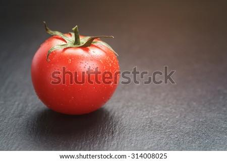 ripe tomato on slate board, vintage toned - stock photo