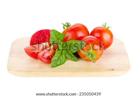 Ripe tomatoes and basil on cutting board. Isolated on white background - stock photo