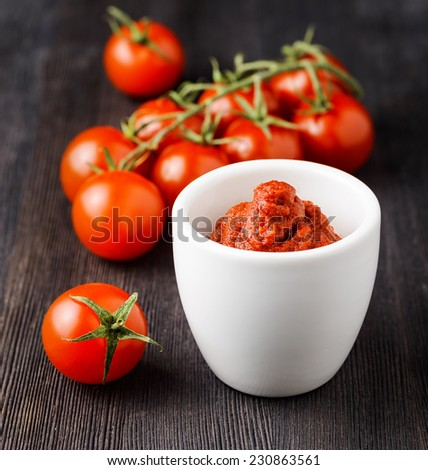 Ripe tomatoes and tomato paste. Ketchup making. - stock photo