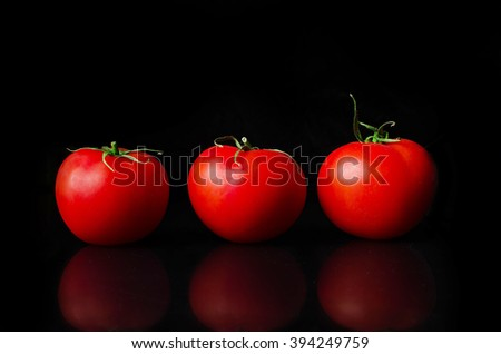 Ripe tomatoes on a black background.Three tomatos on reflective background.Red tomatos. Tomatoes on a dark background. Only red tomatoes.Tomato red. - stock photo
