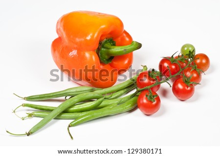 Ripe tomatoes, orange peppers and green beans on white background - stock photo