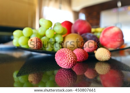 Ripe tropical fruits on a kitchen table - stock photo