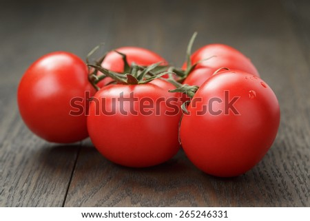 ripe wet tomatoes on vine on wood table - stock photo