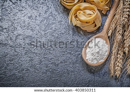 Ripe wheat rye ears wooden spoon flour raw spiral macaroni on black background food and drink concept. - stock photo