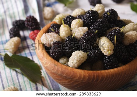Ripe white and black mulberries in a wooden bowl on the table close-up. horizontal - stock photo