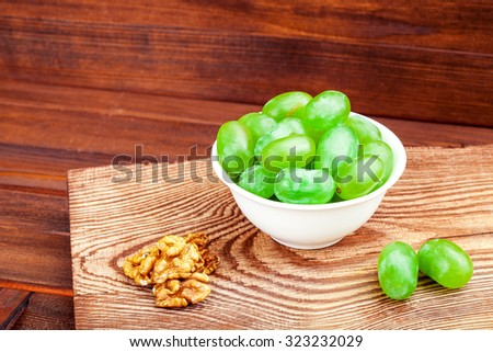 Ripe white grapes in white a plate and a walnut on a wooden support on a wooden table from boards. - stock photo