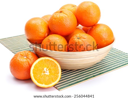 Ripe whole oranges in wooden bowl