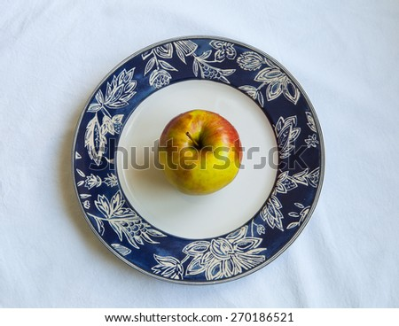 Ripe yellow Apple on a plate, white background - stock photo