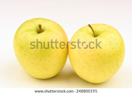 Ripe yellow apple on white background - stock photo