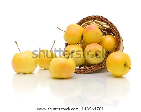 ripe yellow apples in a basket on a white background with reflection - stock photo