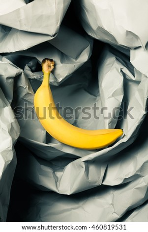 Ripe yellow banana on crumpled gray paper background. Close up. Pop-art style. Studio shot