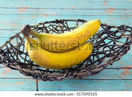 Ripe yellow bananas placed in a metal bowl on a wooden picnic table - stock photo