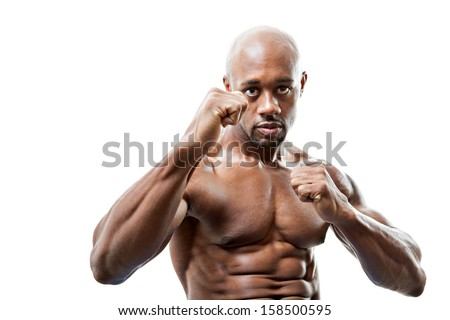 Ripped and muscular martial artist holding his fists up isolated over a white background. Great boxing or fitness concept. Shallow depth of field. - stock photo