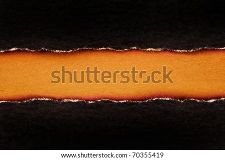 Ripped black paper on brown background - stock photo