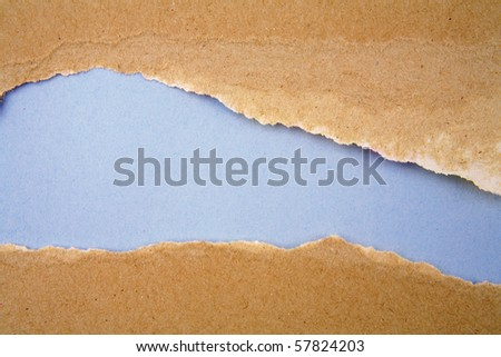 Ripped brown paper on blue background - stock photo