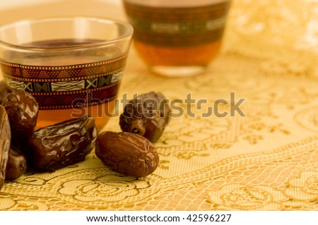 Ripped dates and a cup of tea placed on a golden matt. - stock photo