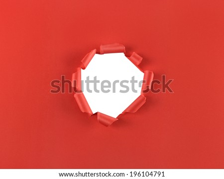 Ripped hole in red paper isolated over a white background - stock photo