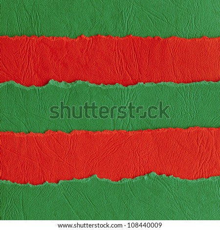 Ripped paper background made of red and green horizontal strips. - stock photo