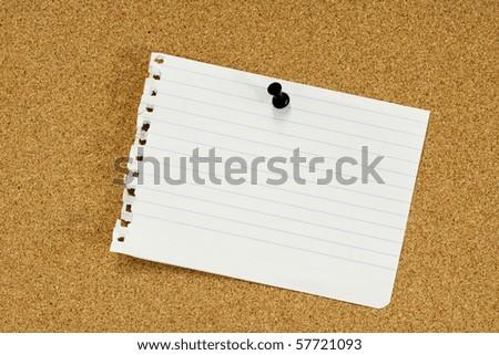 Ripped paper sheet pinned on corkboard - stock photo