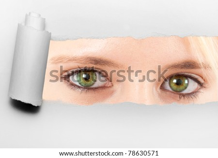 Ripped paper showing green woman's eyes - stock photo