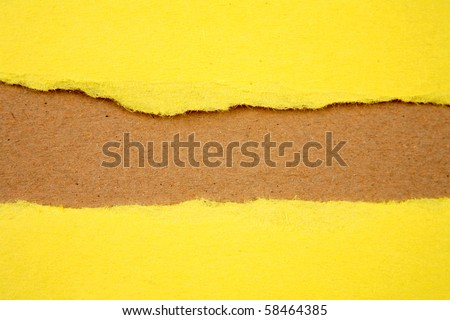 Ripped yellow paper on brown background - stock photo