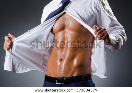 Ripped young man in studio concept - stock photo