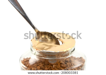 Ripping a hole in the foil of a new jar of instant coffee granules with a teaspoon, isolated on a white background - stock photo