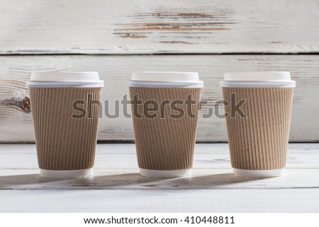 Ripple cups with lids. Three ripple paper cups. White wooden table with cups. Different grades of coffee. - stock photo