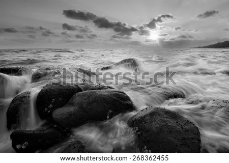 Ripple waves breaking on the rocks at the beach sunset light Focus on rocks foreground black and white tone. - stock photo