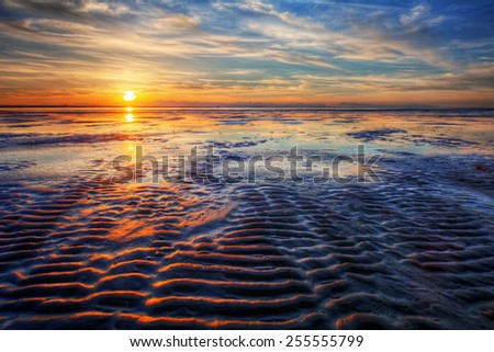 Ripple waves in the ocean at sunset - stock photo