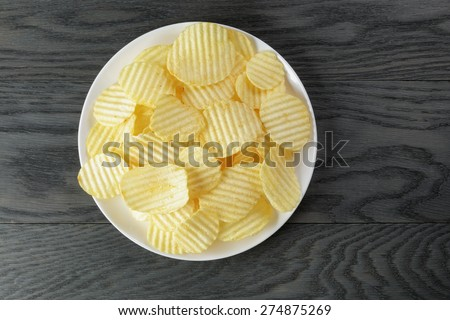 rippled potato chips in white plate on wood table - stock photo