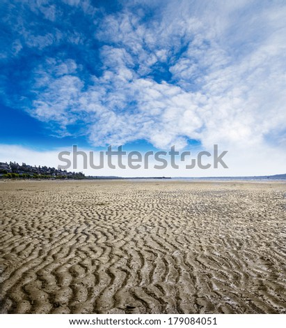 Rippled sand and mud beach created by low tide in White Rock near Vancouver, Canada. Nature background image with copy space.