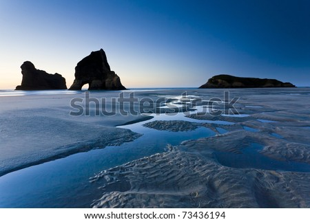 Rippled Sand and rock formations at Wharariki Beach, Nelson, North Island, New Zealand - stock photo
