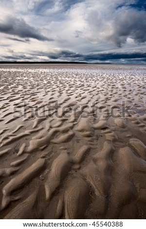 Rippled textures on a beach in Scotland at low tide, with dramatic cloudy sky overhead. Photo taken on West Sands beach in St Andrews shortly before sunset. - stock photo