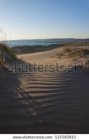 Ripples in sand with dramatic light and lake in background