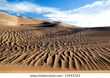 ripples in the sand in front of sand dunes in Colorado - stock photo