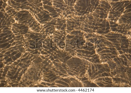 Ripples of light reflecting on river sand - stock photo
