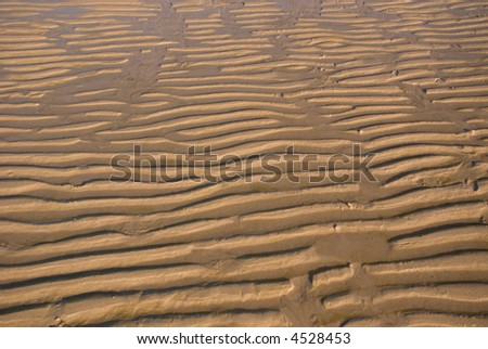 Ripples of Sand caused by tidal water - stock photo