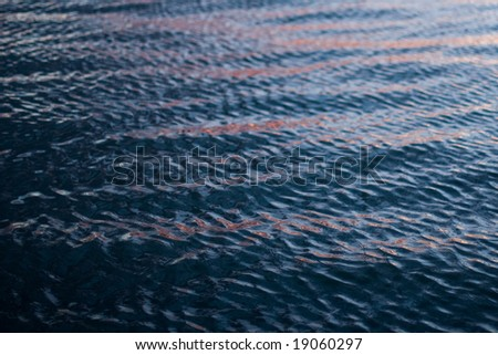 ripples on a lake with a hint of sunset in the reflection - stock photo
