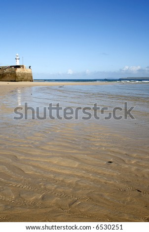 Ripples on the beach and Smeaton's Pier, St. Ives, Cornwall. - stock photo