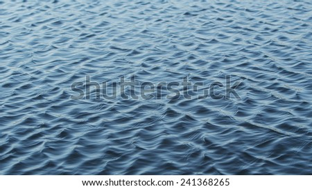 Ripples on the surface of a real water lake - stock photo