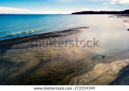 ripples on the transparent azure waves of the surf and the reflection of white clouds - stock photo