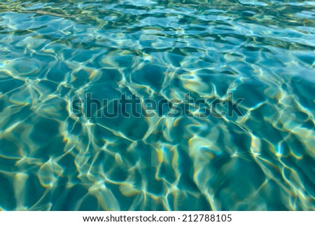 Ripples on the transparent sea water. Sand on the buttom