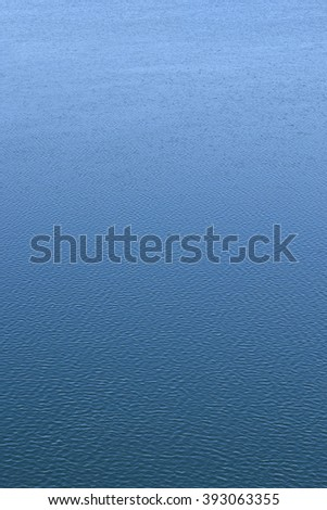 Ripples on the water. Background, vertical position. Blue water of spring river. The water reflects the blue sky. Light ripples.