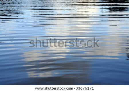 Rippling water background reflecting clouds in the sky. - stock photo