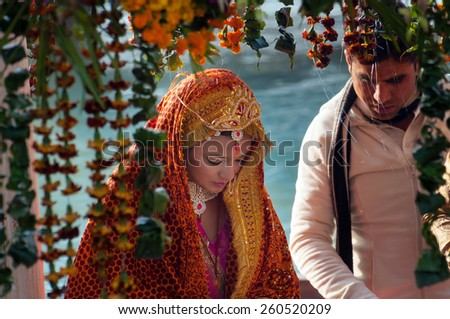 RISHIKESH, INDIA - DEC 12, 2014: Unidentified bride in traditional Indian wedding at temple near River Ganga - stock photo