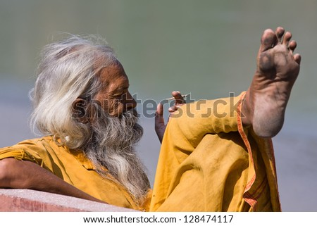 RISHIKESH, INDIA - OCTOBER 24: An unidentified portrait sadhu sits on the ghat along the Ganges on October 24, 2012 in Rishikesh, India. Tourism has drawn many alleged fake sadhus to Rishikesh