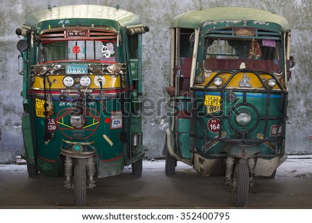 RISHIKESH, INDIA - OCTOBER 19, 2014 : Auto rickshaw taxis on a road. These iconic taxis have recently been fitted with CNG powered engines in an effort to reduce pollution