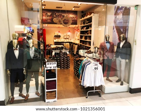 RISHON LE ZION, ISRAEL- DECEMBER 29, 2017: Modern clothes in a shop on a hanger. Shirts and sweaters of different colors and denim for youth. Clothes of different styles on the hanger in the showroom.