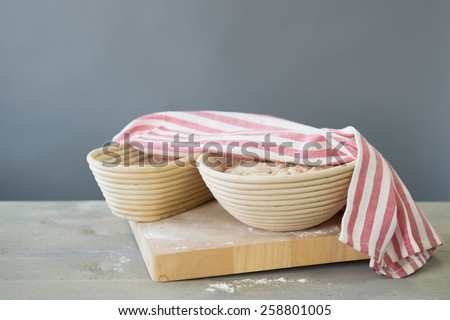 Rising bread dough in banneton - stock photo
